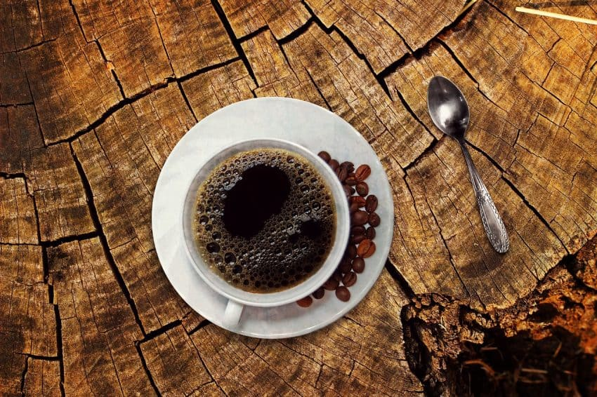 Image shows cup of coffee seen from above with beans on the plate.