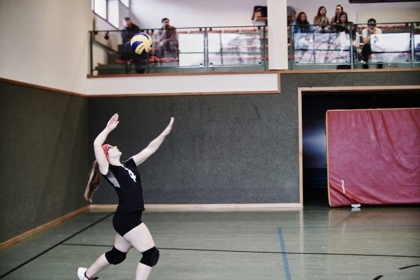 Atleta saca a bola em quadra sob olhar atento de alguns espectadores.