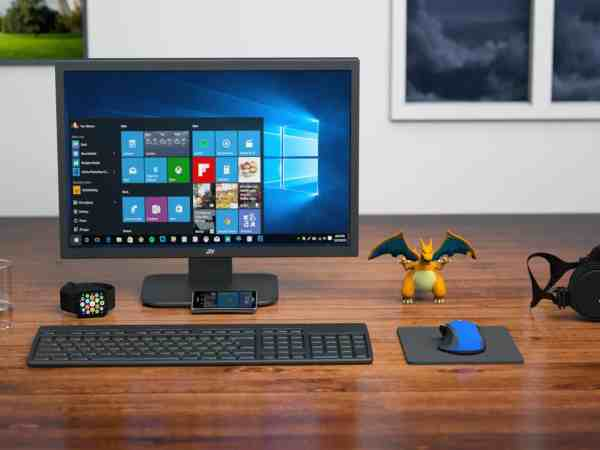 Imagem mostra mesa com computador e acessórios, como fone de ouvido, mouse e mouse pad.