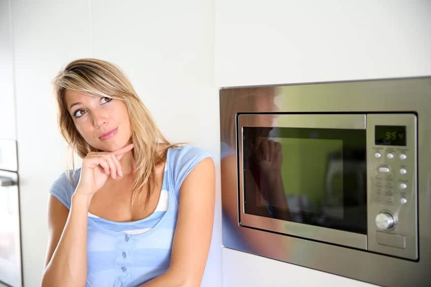 mulher com cara de pensativa ao lado de um micro-ondas