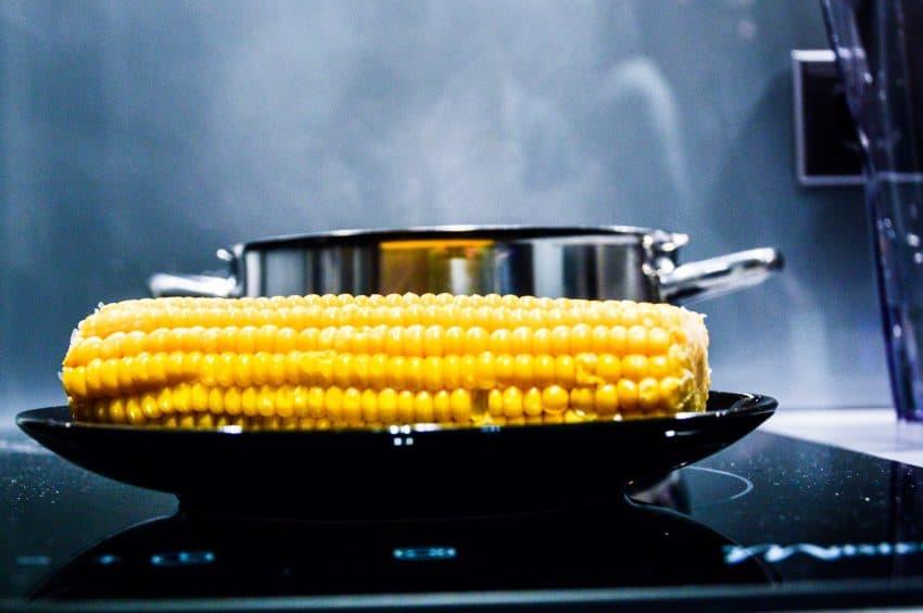 Na imagem, um milho é cozido em uma panela de ferro fundido e atrás uma panela de aço inox cozinha outro alimento.
