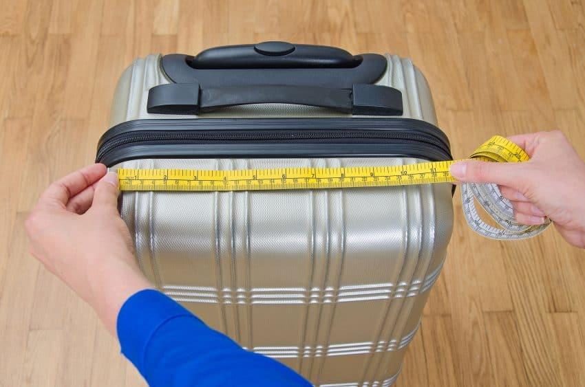 Mãos de mulher medindo mala de viagem com fita métrica.