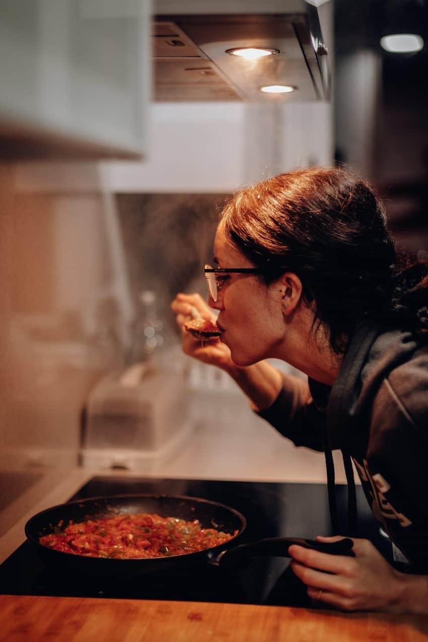 Imagem de uma mulher cozinhando em um fogão eletromagnético.