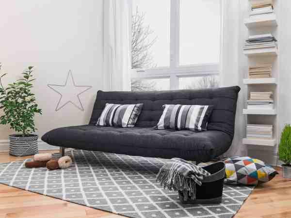 Sofá-cama fechado na sala, sobre tapete, com janela atrás e estante.