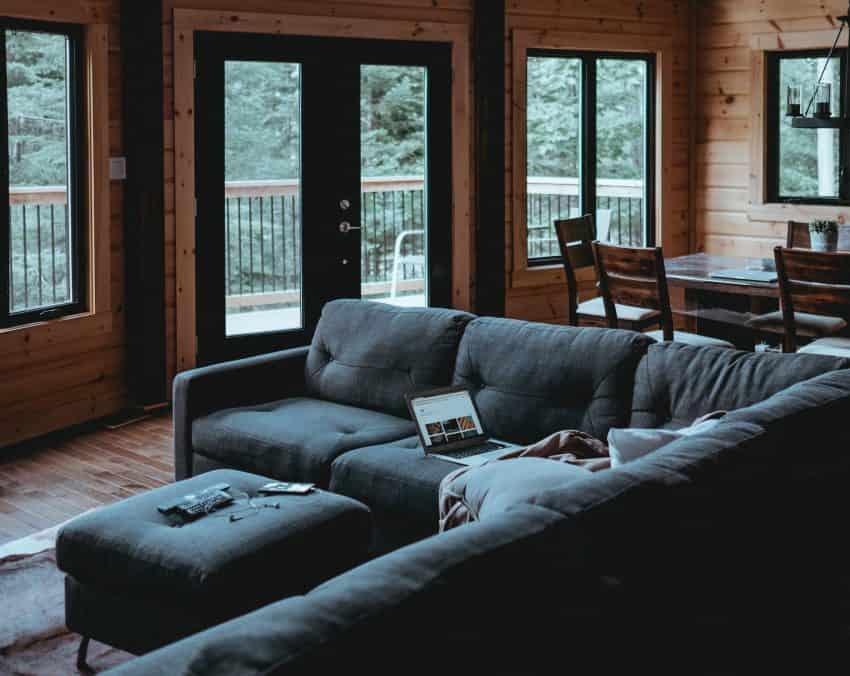 Imagem mostra um sofa cinza grande em sala.