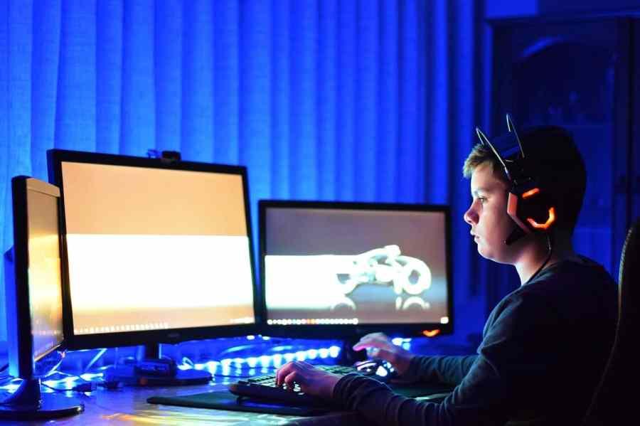 Imagem mostra um menino sentando em uma mesa em frente a três monitores