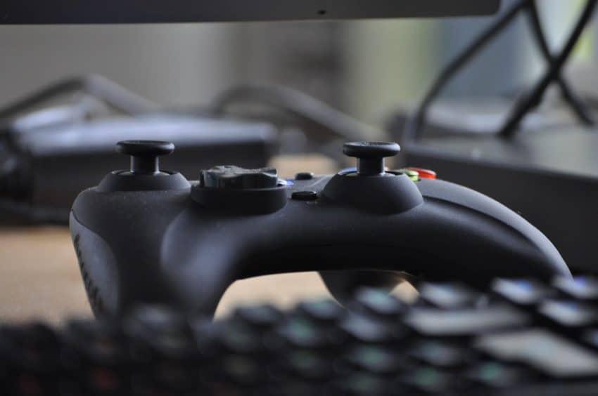 Imagem mostra um controle para Xbox One em cima de uma mesa perto de um teclado de computador.