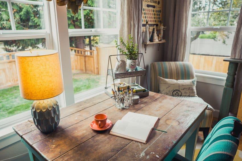 Imagem mostra um pequeno escritório caseiro, bastante iluminado e decorado. No centro da foto, uma mesa de madeira acomoda um abajur, uma xícara e um pires e um caderno aberto.