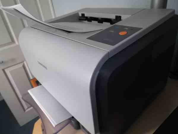 Close de uma impressora a laser com papel na bandeja.