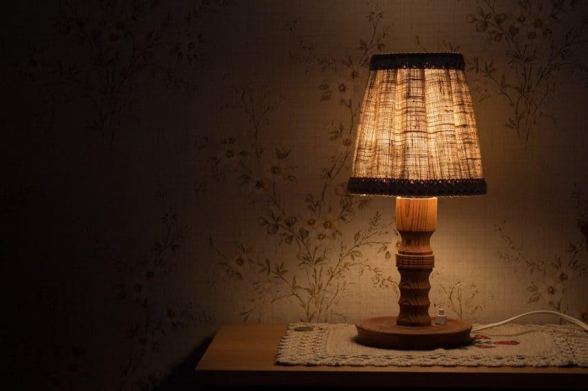 Imagem mostra uma pequena luminária de luz difusa sob um criado-mudo, iluminando um quarto escuro, com um papel de parede de ramos de flores.
