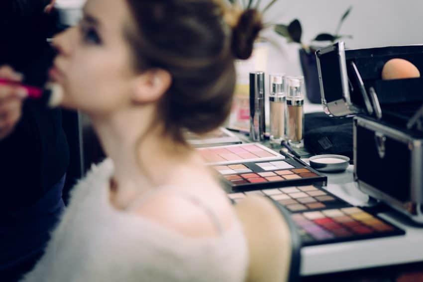 Na imagem vê-se uma moça sendo maquiada e ao fundo diversas paletas de sombra e outras maquiagens em cima de uma mesa.