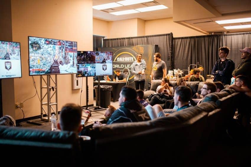 Imagem mostra uma sala com TVs e pessoas sentadas em sofás jogando videogame.