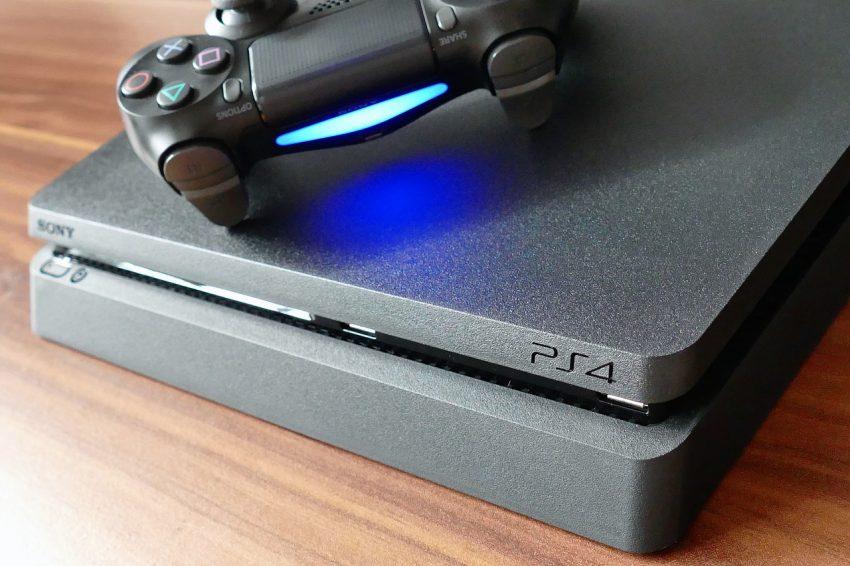 Imagem mostra um console de Ps4 e um controle na cor preta sobre uma mesa de madeira.