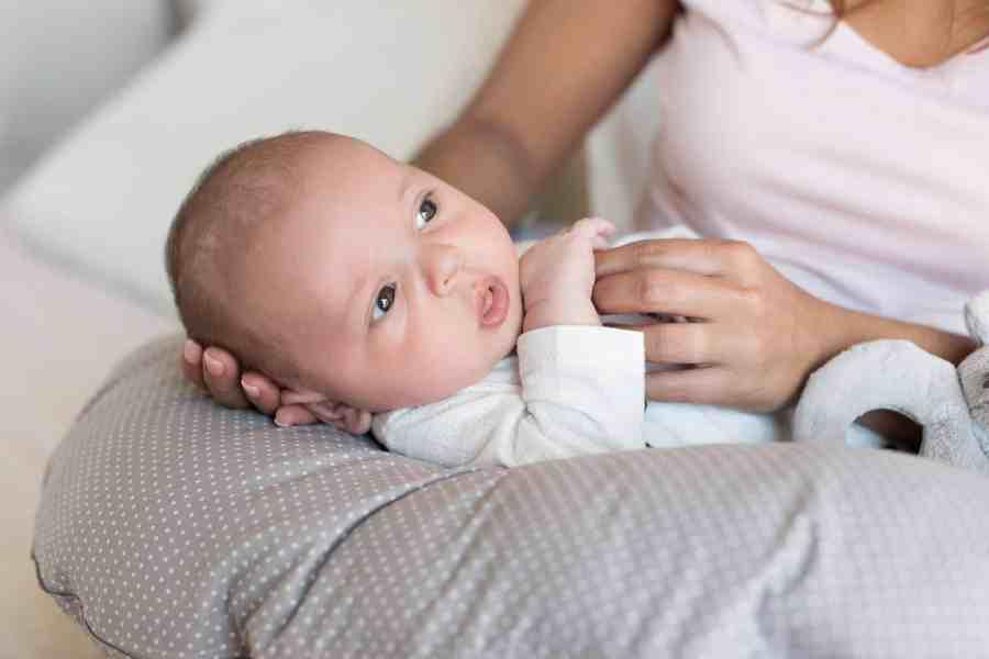 Imagem de um recém-nascido deitado em almofada de amamentação.