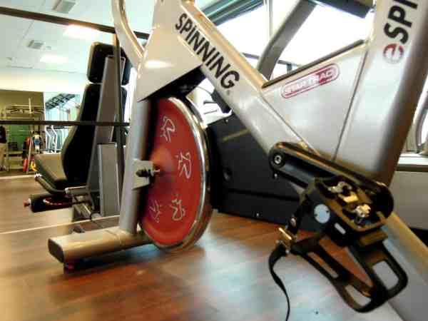 Imagem mostra uma bicicleta de spinning próxima a uma cadeira extensora e ao fundo alguns outros equipamentos de academia.