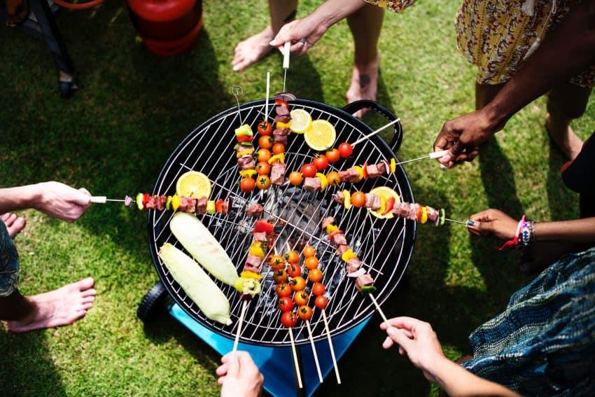 Imagem de um grupo de pessoas assando espetinhos na churrasqueira.