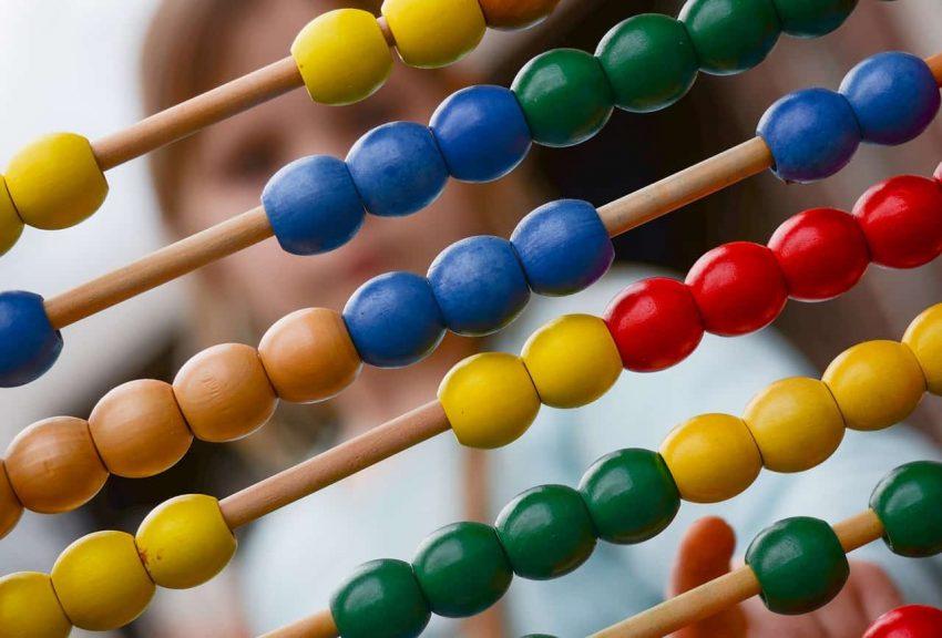 Hastes de madeira do ábaco com contas coloridas e crianças ao fundo.