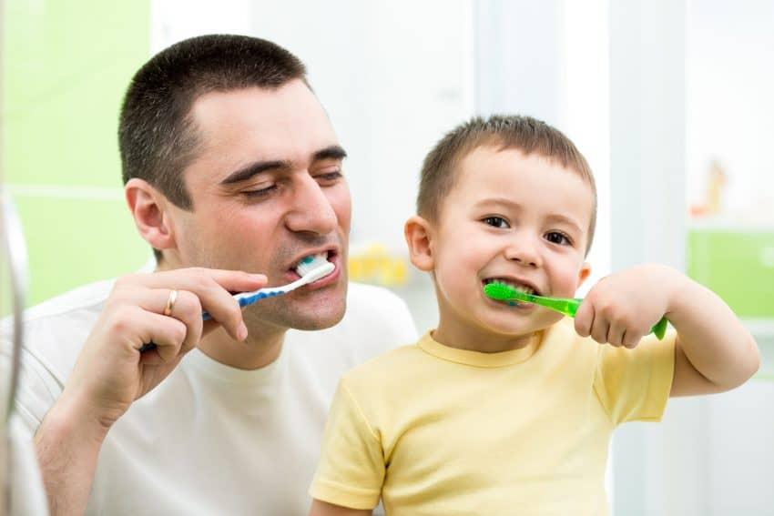 Pai e filho escovando os dentes juntos.