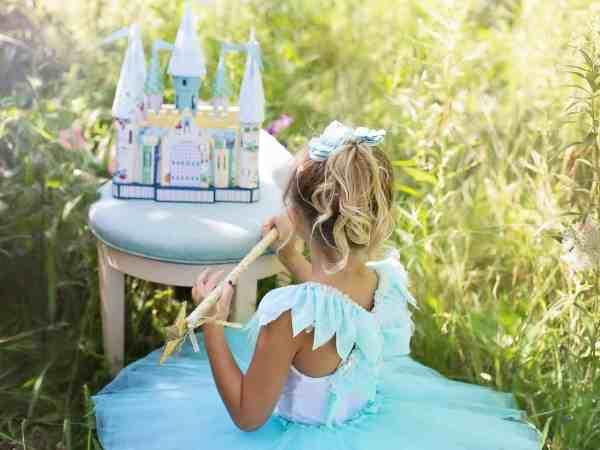 Imagem de menina com vestido azul de princesa, enfeite de cabelo e varinha de condão com castelo de fantasia sobre banco acolchoado em jardim.