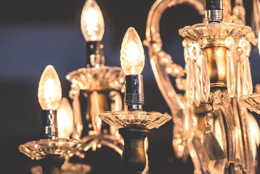 Imagem de lustre em estilo clássico, com lâmpadas amareladas.