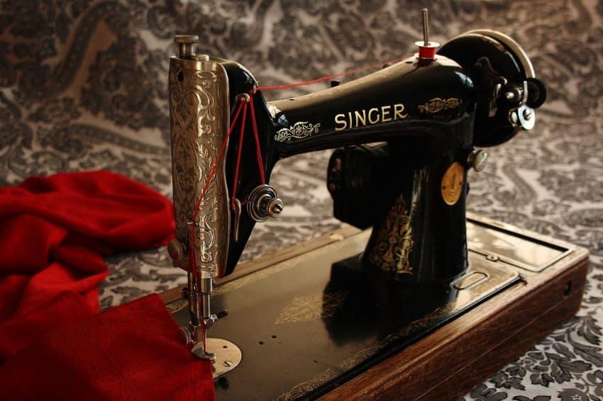 Imagem mostra uma máquina de costurar antiga, da marca Singer.
