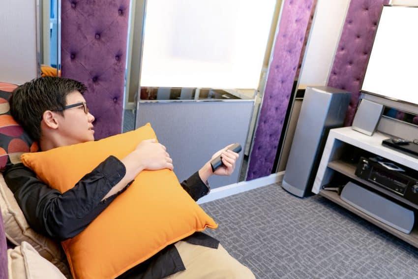 Homem deitado no sofá segurando almofada e controle mudando o canal da tv em uma sala.