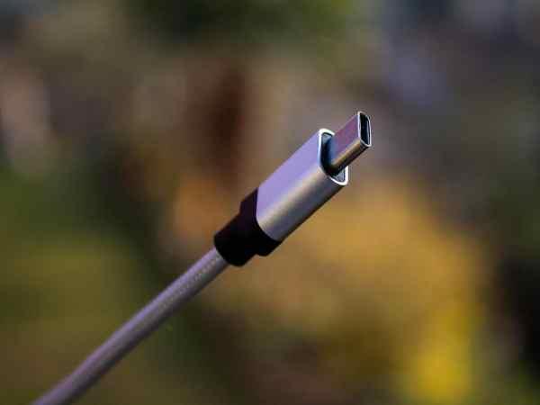 Imagem mostra um conector USB tipo C e um fundo desfocado.