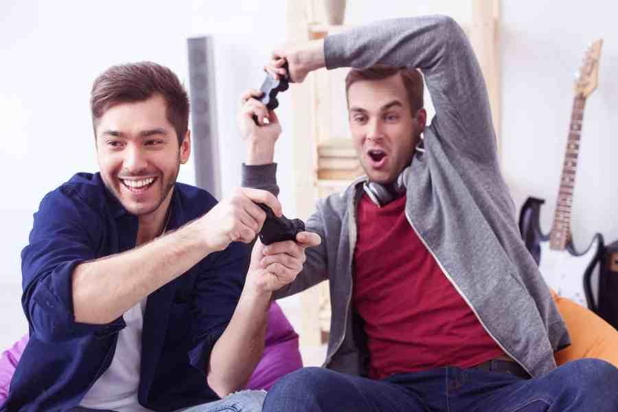 Imagem mostra dois amigos jogando videogame e se divertindo muito.