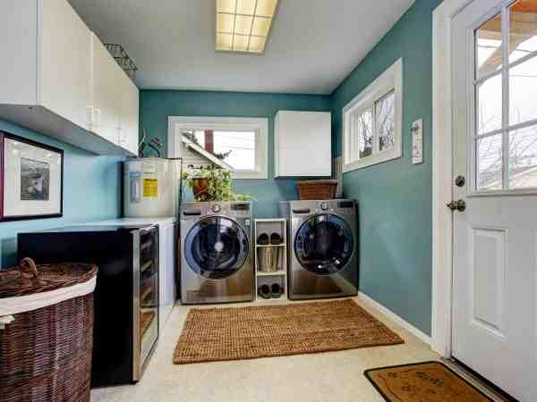 Lavanderia com armários e máquinas de lavar e secar.