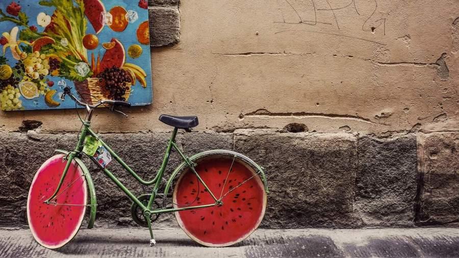 Imagem de bicicleta estacionada com rodas desenhadas com um estilo de melancia.