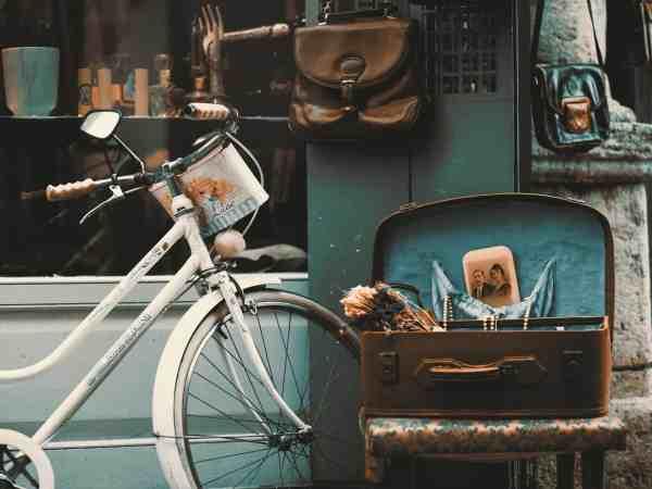 Bicicleta vintage próxima a uma maleta com objetos antigos.