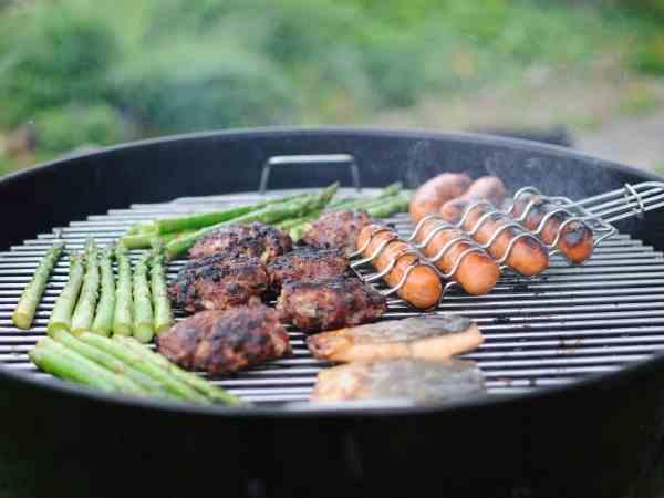 Foto de uma churrasqueira portátil grelhando aspargos e carnes.