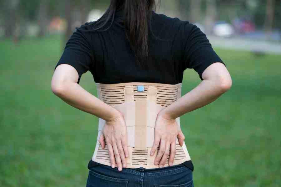 Imagem de uma mulher usando um corretor de postura bege.