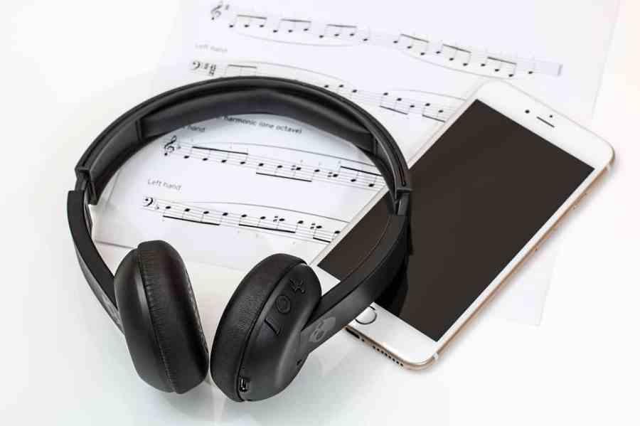 Fone de ouvido supra-auricular com celular e partitura de música.