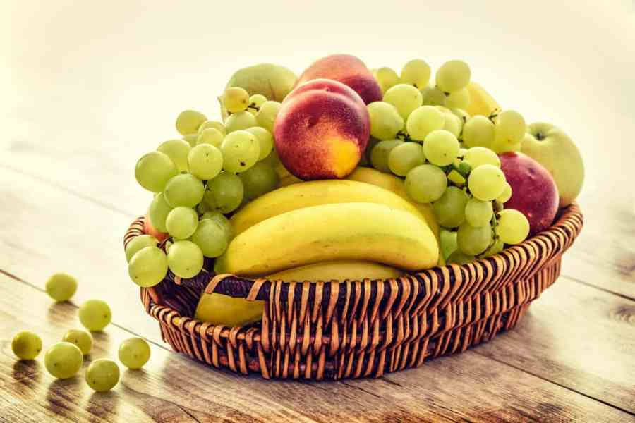 Foto de uma fruteira de material semelhante à palha, contendo bananas, uvas e pêssegos.