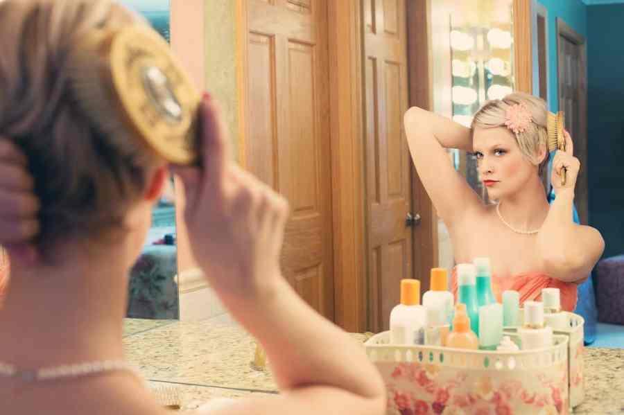 Imagem de mulher penteando cabelo e fazendo maquiagem em frente a espelho.