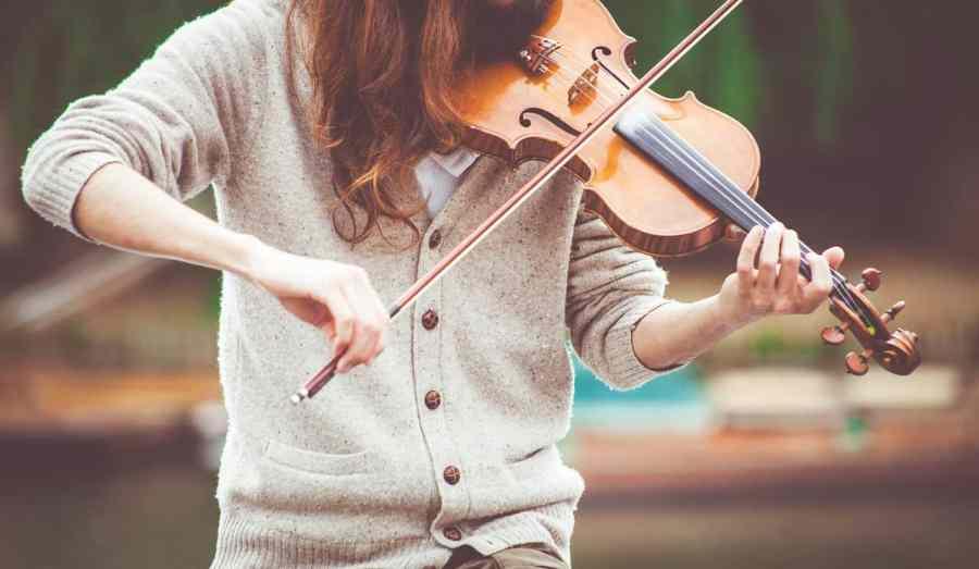 Foto de uma garota tocando um violino.