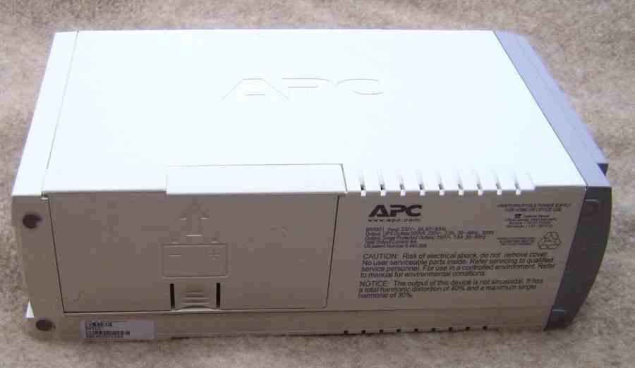 Imagem mostra a parte traseira de um nobreak branco da marca APC.