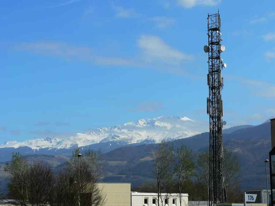 Imagem mostra uma paisagem com alpes ao fundo e uma torre de transmissão.