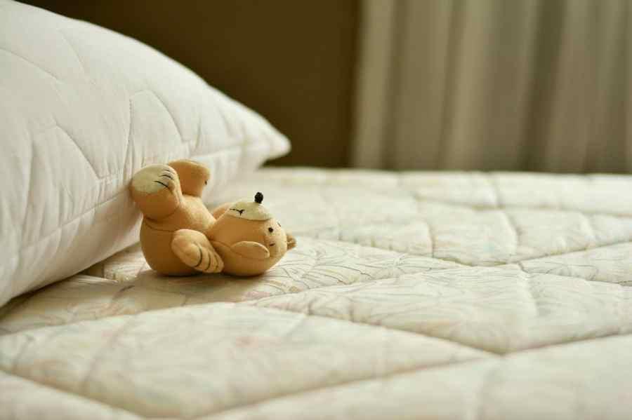 Colchão e travesseiro e um ursinho de pelúcia.