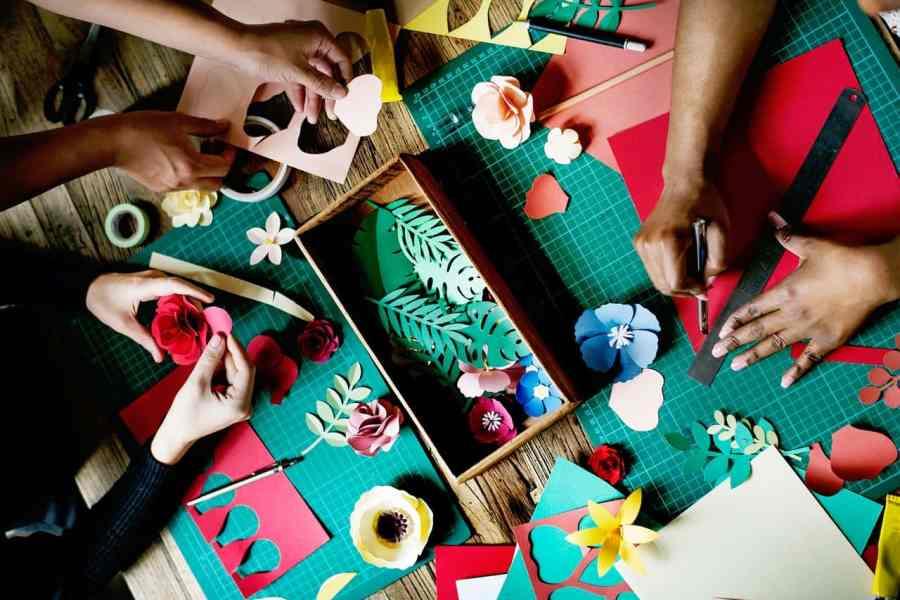Mesa de madeira com várias mãos fazendo artesanatos em cima de bases de corte.