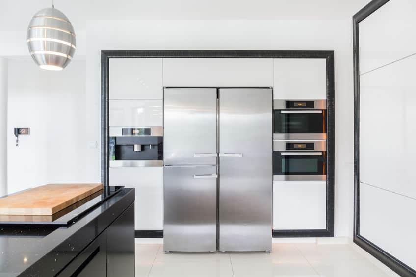 Imagem de geladeira grande de inox em cozinha.