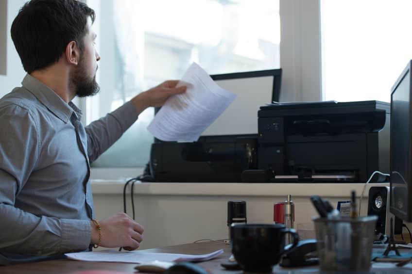Homem sentado em uma mesa mexendo em um scanner.