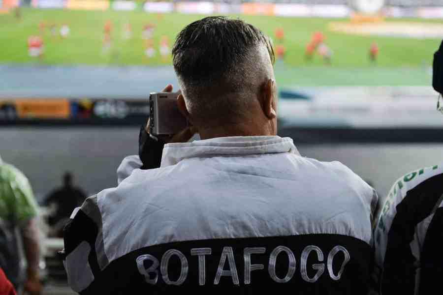 Homem de costas usando rádio portátil em estádio de futebol