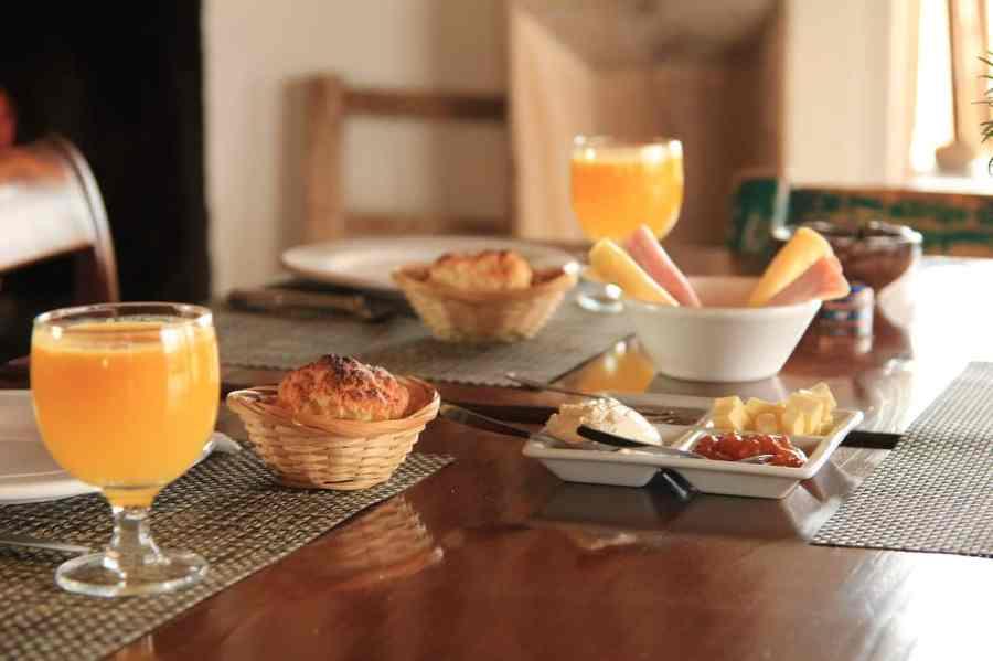 Mesa montada de café da manhã para duas pessoas, com suco de laranja em taças de vidro, pratos, pães, queijo e presunto aos centro.