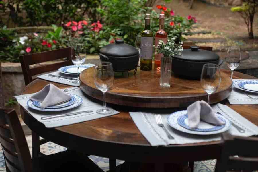 Imagem de mesa de jantar de madeira com jogo de sousplat de louça branca com azul.