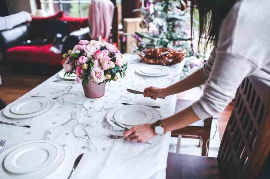 Imagem de mulher preparando a mesa com talheres e pratos com suporte de sousplat de louça branca.