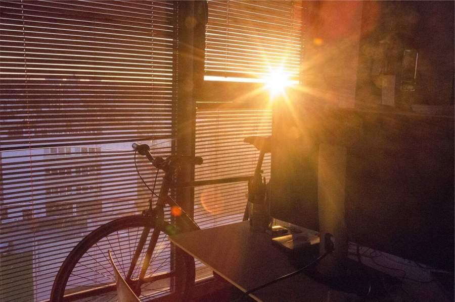Uma bicicleta encostada em um janelão fechado por uma persiana com os raios de sol invadindo o ambiente.