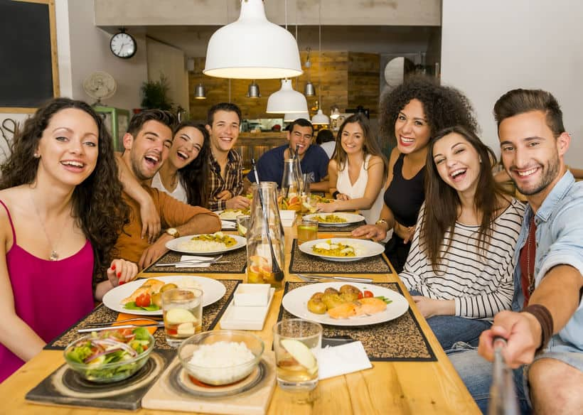 Imagem de pessoas em mesa com seus pratos almoçando.
