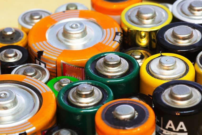 Imagem mostra uma fileira com treze pilhas recarregáveis, de embalagens diferentes. Apenas as três pilhas centrais estão nítidas.